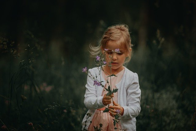A girl demonstrating her love of flowers, and value of nature.